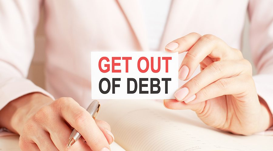 Woman writes in a notebook with a silver pen and hand hold card with text: GET OUT OF DEBT. Pink background, front view. Business and education concept.